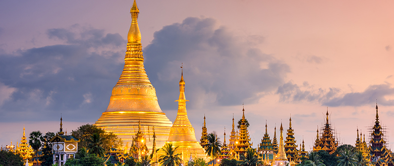 The Shwedagon Pagoda's golden spires glow with the setting sun.